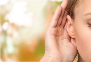 Woman holding hand up to ear to listen